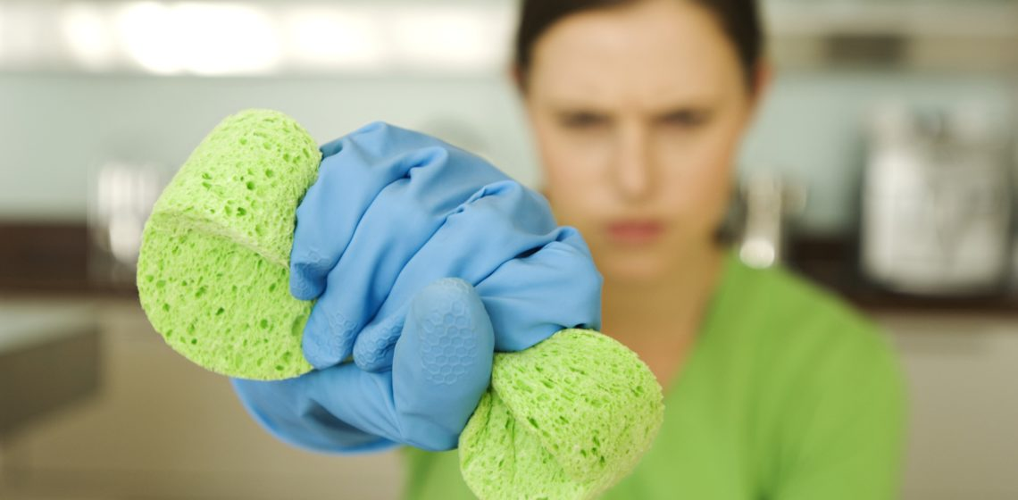 Young woman wringing sponge